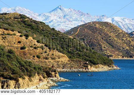 Barren Hills With Snow Covered Mountains Beyond Surrounding Silverwood Lake, Ca Taken At The Rural M