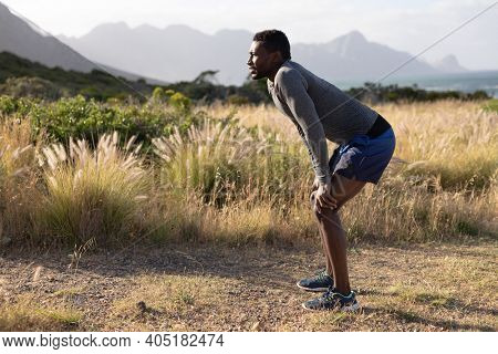 Fit african american man in sportswear resting leaning on knees in tall grass. healthy lifestyle, exercising in nature.