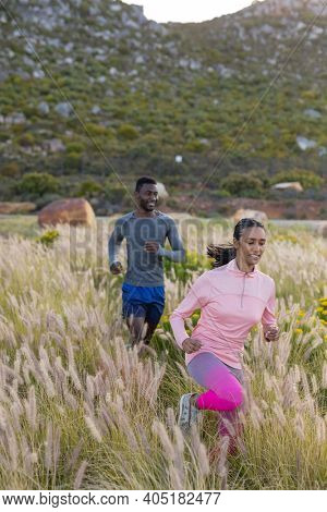 Fit african american couple in sportswear running through tall grass. healthy lifestyle, exercising in nature.