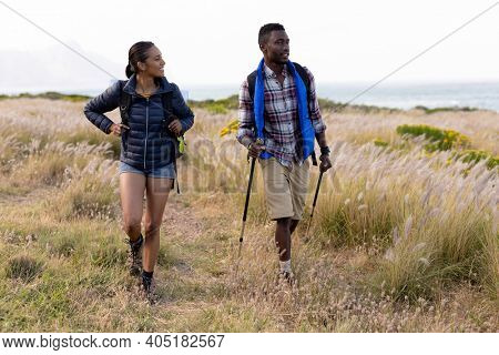 Fit african american couple wearing backpacks nordic walking on coast. healthy lifestyle, exercising in nature.