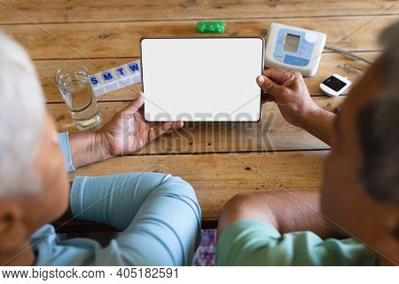 Senior african american couple with medication using digital tablet at kitchen table. retirement lifestyle in self isolation during coronavirus covid 19 pandemic.