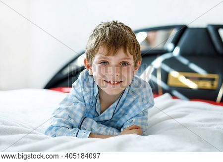 Adorable Happy Little Kid Boy After Sleeping In His White Bed In Colorful Nightwear. School Child Ce
