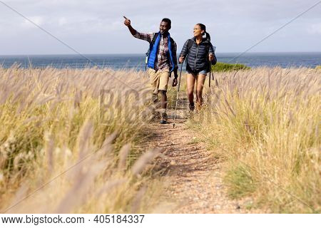Fit afrcan american couple wearing backpacks nordic walking with poles in mountain countryside. healthy lifestyle, exercising in nature.