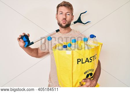 Young caucasian man holding recycling bag with plastic bottles and waste picker looking at the camera blowing a kiss being lovely and sexy. love expression.