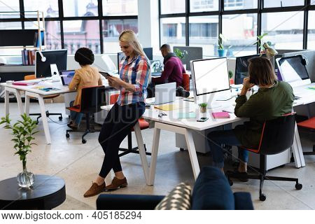 Caucasian businesswoman working in creative office. woman leaning on desk and using tablet computer, with colleagues in the background. business people and work colleagues at a busy creative office.