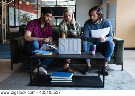 Diverse group of business people working in creative office. group of people using laptop and discussing work. business people and work colleagues at a busy creative office.