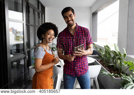 Two mixed race business people working in creative office. portrait of two people looking at camera and smiling. business people and work colleagues at a busy creative office.