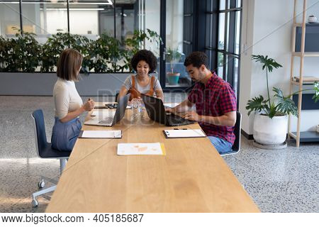 Diverse group of business people working in creative office. group of people sitting and discussing work. business people and work colleagues at a busy creative office.