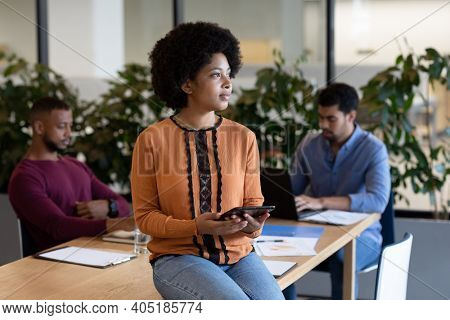 Diverse group of business people working in creative office. woman sitting on a table and using tablet. business people and work colleagues at a busy creative office.