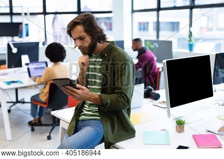 Caucasian businessman leaning on desk using tablet computer in creative office. business people and work colleagues at a busy creative office.