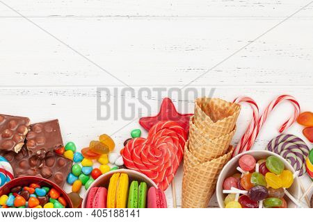 Various sweets assortment. Candy, bonbon and macaroons on wooden background. Top view flat lay with copy space