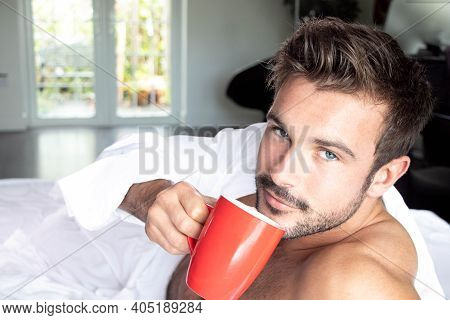 Handsome Hairy Naked Muscular Man With Beard Sixpack Abs Lying In Bed Covered With Sheet Drinking Co