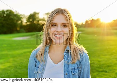 Portrait Of Smiling Beautiful Happy Young Woman 20 Years Old, Sunset Green Lawn In Park Background