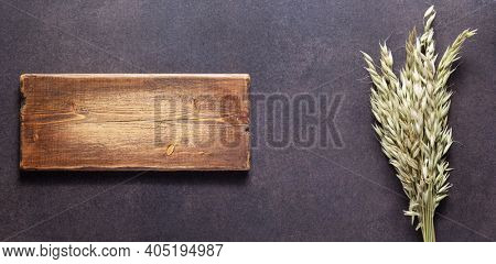 Bunch or bundle of oat at table. Natural food concept at stone rustic background texture. Flat lay panoramia or panoramic top view