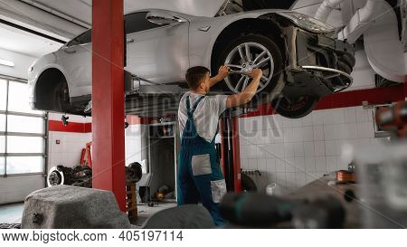 Rear View Of Young Caucasian Mechanic Screwing Wheel Of Auto Raised On Industrial Lift On Car Servic