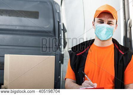 Portrait of a smiling deliverer, delivery boy, covid coronavirus concept