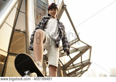 Low Angle View Of A Fifteen-year-old Asian Teenage Boy Standing On A Skateboard