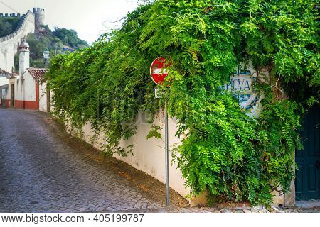 Obidos, Portugal, October 05, 2018: Road Sign Is On Side Of The Road In The Thickets Of Bushes And T