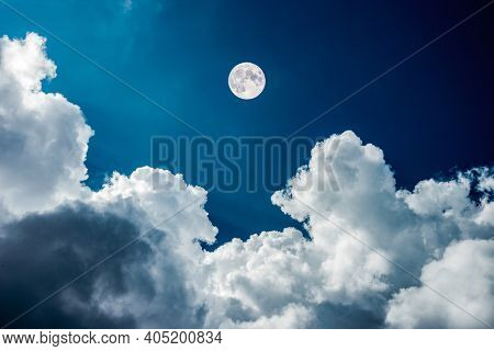 Magical view of a nighttime sky with clouds with large full moon. Attractive astronomy phenomenon. Halloween design background concept. Exotic photo wallpaper. Image of ominous sky.