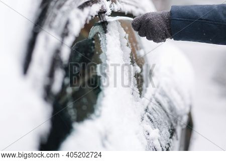 Close Up Of Man Is Cleaning Snowy Window On A Car With Snow Scraper. Focus On The Scraper. Cold Snow