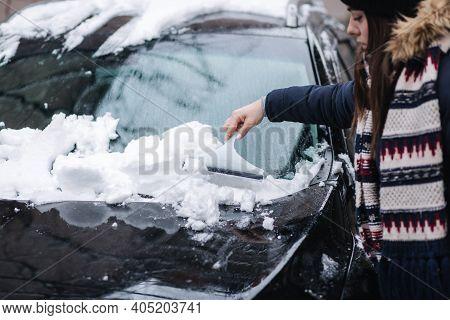 A Woman Is Cleaning Snowy Window On A Car With Snow Scraper. Pretty Woman Warmy Dressed Clean Her Ca