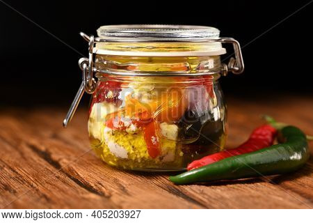 Feta Cheese, Pickled Peppers And Olives In A Storage Jar On The Wooden Table.