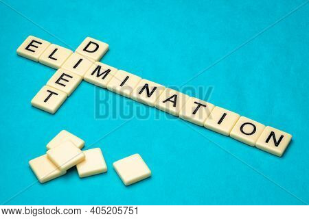 elimination diet  crossword in ivory letter tiles against textured handmade paper, food allergy and healthy eating concept