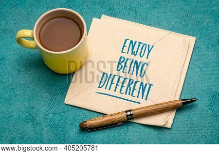 Enjoy being different - inspirational note, handwriting on a napkin with a cup of coffee, nonconformism, career, education and personal development concept