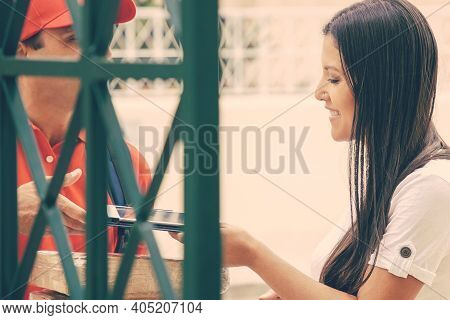 Happy Woman Receiving Parcels, Standing At Gate Outside, Using Couriers Tablet For Confirming Receiv
