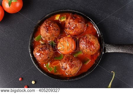 Stewed Meatballs In Tomato Sauce In A Pan On A Dark Background, Top View.