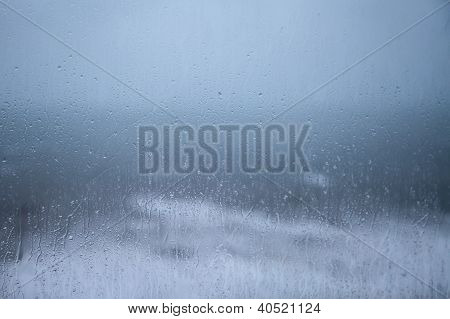 Rainy Holiday? Raindrops On Window Pane With Cloud And Sea Background.