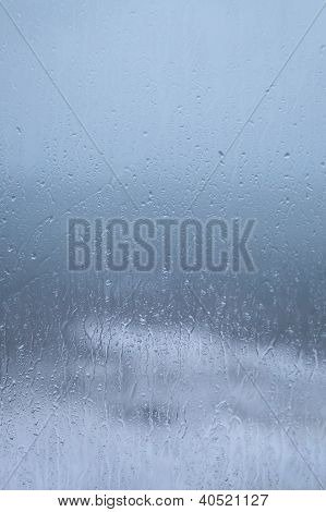 Rainy Holiday? Raindrops On Window Pane With Cloudy Weather And Sea Background.