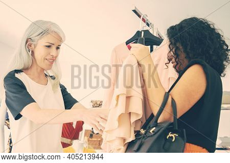 Happy Women Shopping Together And Discussing Chosen Dress In Fashion Store. Side View. Consumerism O