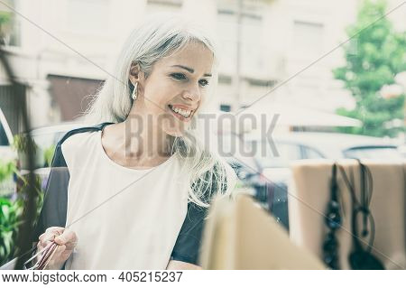 Cheerful Female Shopper Looking At Accessories In Shop Window, Holding Shopping Bags, Standing At St