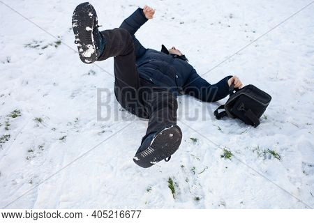 A Man Falls In The Snow. The Man Slipped And Was Injured. Falling On Ice. Winter. Fracture, Bruise,