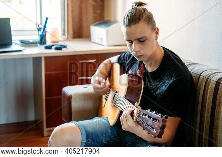 Online Guitar Lessons. Caucasian Teenager Playing Guitar, Having Online Guitar Lessons, Enjoying Fav