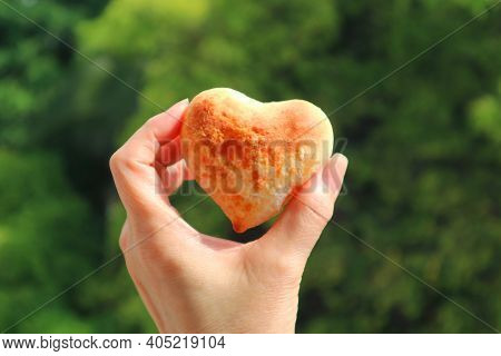 Lovely Heart Shaped Homemade Pao De Queijo Or Brazilian Cheese Bread In Woman's Hand Against Blurry