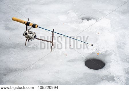 Fishing On A Frozen Lake In Winter With Fishing Pole Or Rod, Ice Auger And Equipment For Fishing Wit