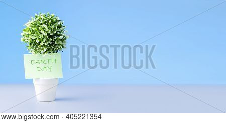 World Environment Day Concept: Note With Words Earth Day On Green Tree Against Blue Background.