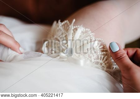Woman Wearing A Garter On The Leg. The Bride Holds In Hand Close-up Garter In Hotel Room. Morning Pr