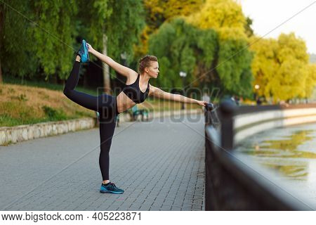 Full Length View Of A Fit Cheerful Athletic Sportswoman In Black Sportwear Workout On Sidewalk In Th