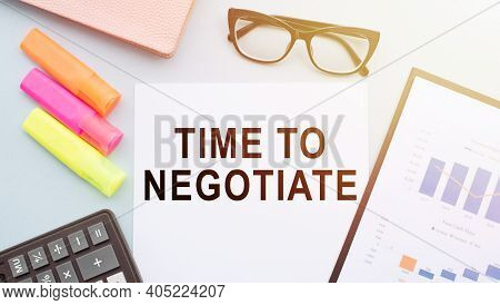 The Text Time To Negotiate On Office Desk With Calculator, Markers, Glasses And Financial Charts.