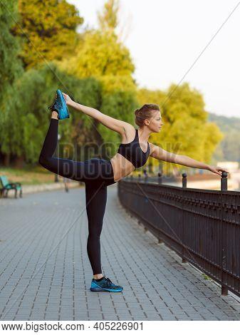 Full Length View Of A Fit Athletic Sportswoman In Black Sportwear Workout On Sidewalk In The Park, D