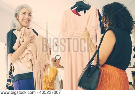 Cheerful Woman Showing Chosen Dress With Hanger To Her Friend And Laughing. Two Ladies Shopping In F