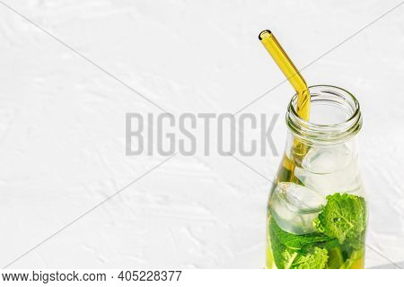 Bottle With Lemonade And Glass Straw On White Background. Drink With Fresh Lemons. Water With Lemon,