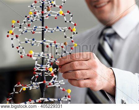 Teacher examining DNA model in science class