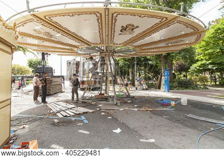 La Coruna - Spain - August 01, 2012: Some Workers Dismantle A Carousel In The Avenue De Los Jardines