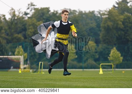 Youth Football Player Running With Parachute. Soccer Football Endurance Training. Speed Or Sprint Te