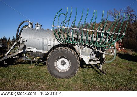 Silver Manure Wagon Without Tractor With Green Hoses Standing On An Autumn Meadow In The Morning, Su