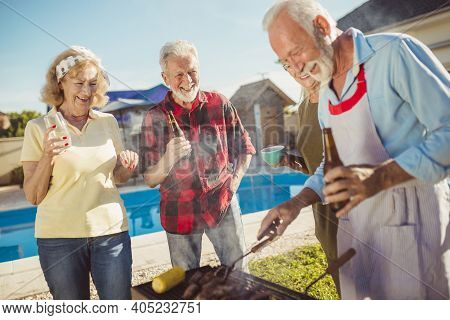 Group Of Senior Friends Having A Backyard Barbecue Party By The Swimming Pool, Gathered Around The G